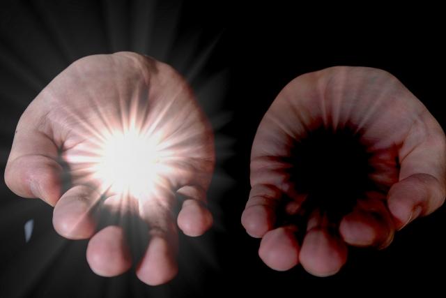 光と闇を持つ男性の手