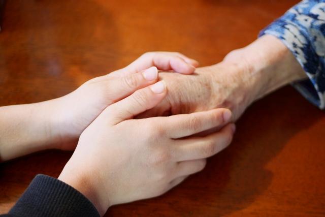 高齢者の手を握る子供の手